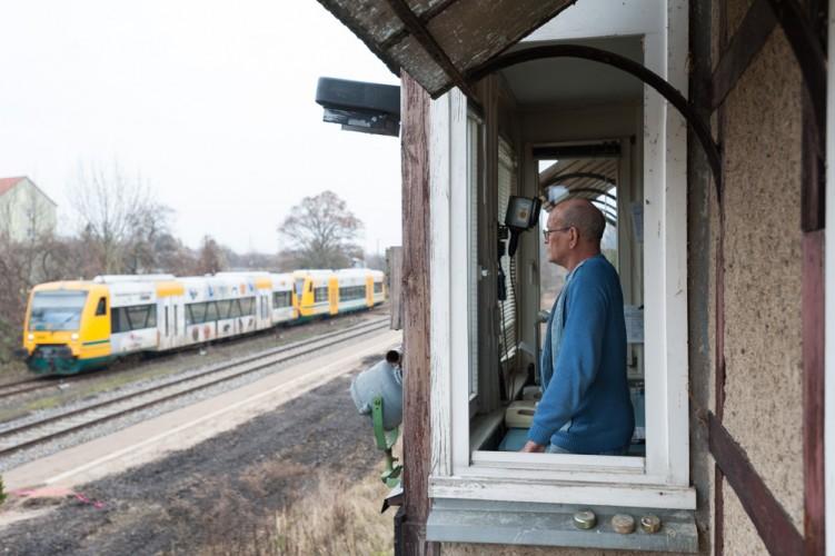 Schrankenwärter Burkhard Winter blickt aus dem Stellwerk auf einen ODEG-Triebwagen