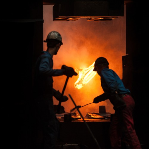 Arbeiter streuen Sand auf den Schmiedehammer, dahinter ein glühendes Werkstück
