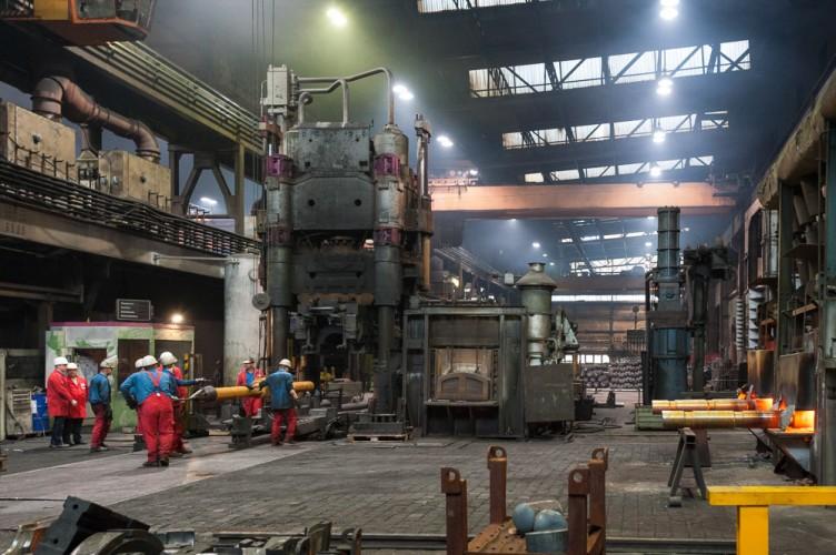 Arbeiter in der dunstigen Werkshalle der Wildauer Schmiedewerke