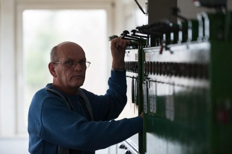 Weichen- und Schrankenwärter Burkhard Winter gibt am Blockkasten eine Fahrstraße frei