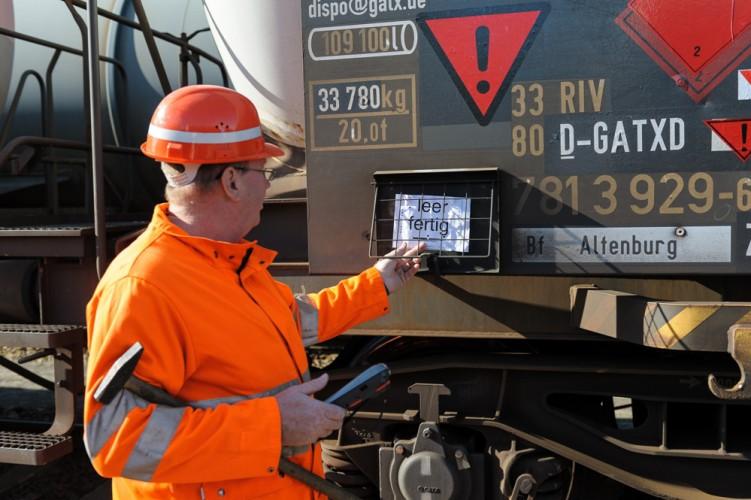 Der Wagenmeister leert den Zettelhalter für Transportscheine an einem Kesselwagen