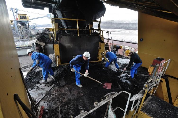 Arbeiter entfernen mit Schippen die ausgeschüttete Braunkohle auf dem Schaufelradbagger