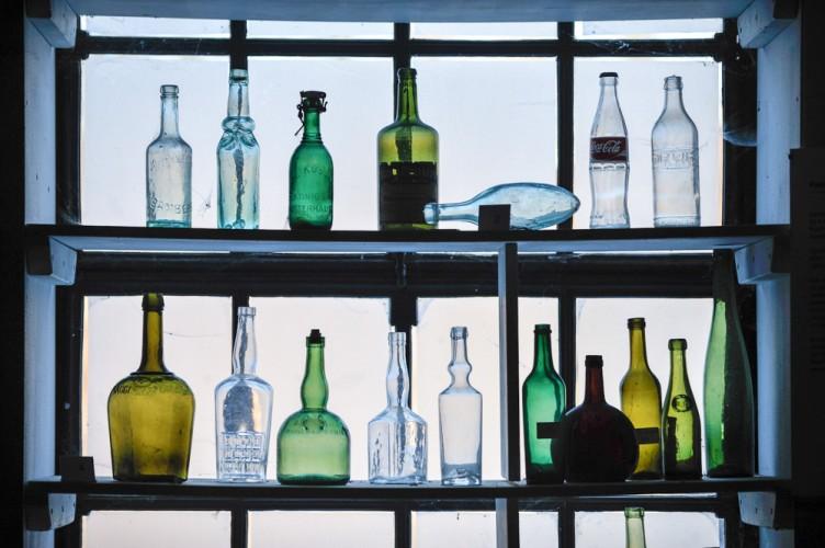 Farbige Glasflaschen vor einem Fenster der Glasbläserei
