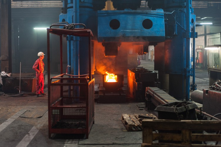 Arbeiter an einem Schmiedestück in der Maschinenhalle der Wildauer Schmiedewerke