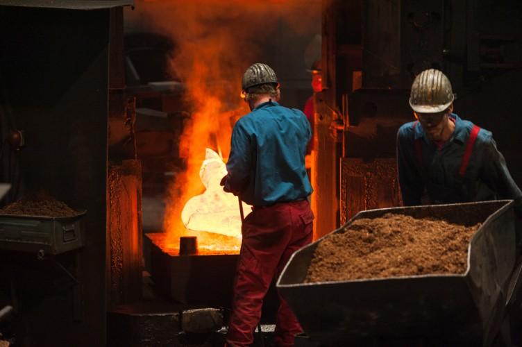 Arbeiter des Schmiedewerks transportieren Sand zum Schmiedehammer