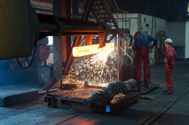 Arbeiter der Schmiedewerke schweißen an einem glühenden Schmiedestück