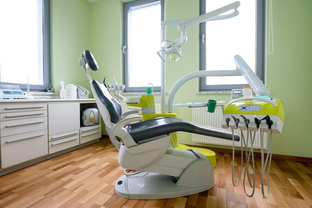 Zahnarztstuhl in grünem Behandlungszimmer
