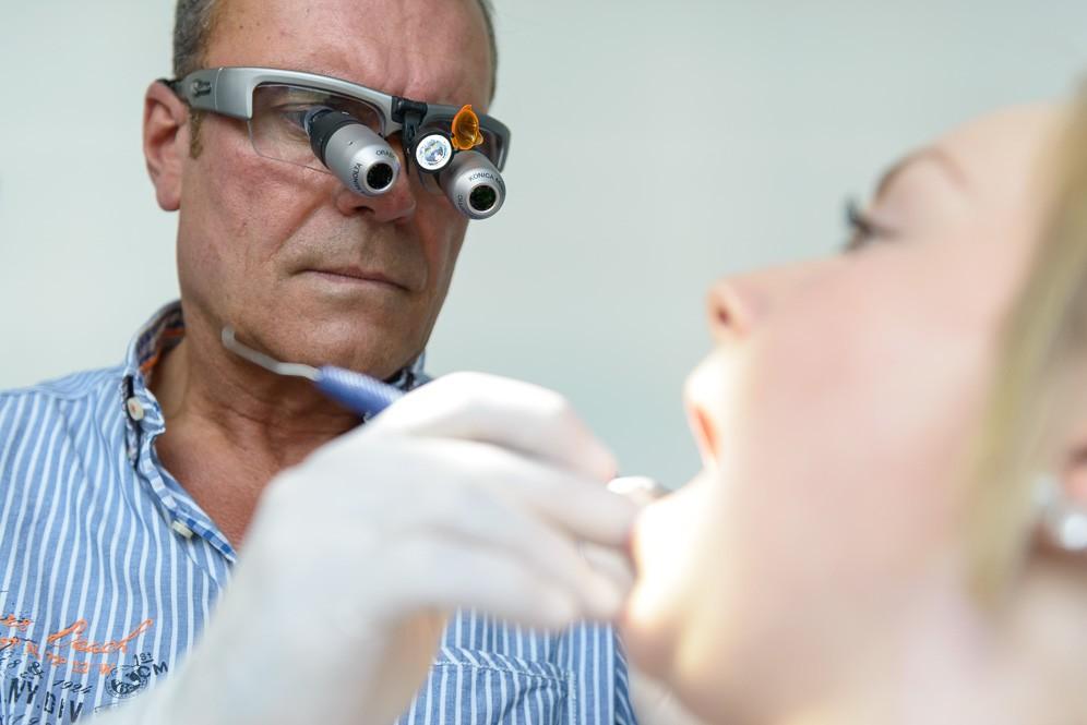 Zahnarzt mit Lupenbrille während Behandlung einer Patientin