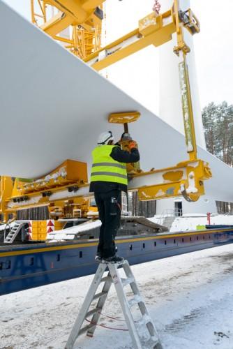 Ein Techniker befestigt das Rotorblatt in der Kran-Traverse, Windpark-Baustelle bei Wahlsdorf, Brandenburg