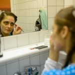Klinikclown Hella Propella zieht ihre Augenbrauen clownstypisch nach
